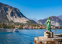 Italy, Piedmont, near Stresa: Isola dei Pescatori (also known as Isola Superiore), one of the five Borromean Islands (Isole Borromee) of lake Lago Maggiore, statue of praying Madonna at harbour entrance and view towards town Baveno | Italien, Piemont, bei Stresa: Isola dei Pescatori (auch Isola Superiore genannt), eine der fuenf Borromaeischen Inseln im Lago Maggiore, Statue der betenden Madonna an der Hafeneinfahrt und Blick auf Baveno