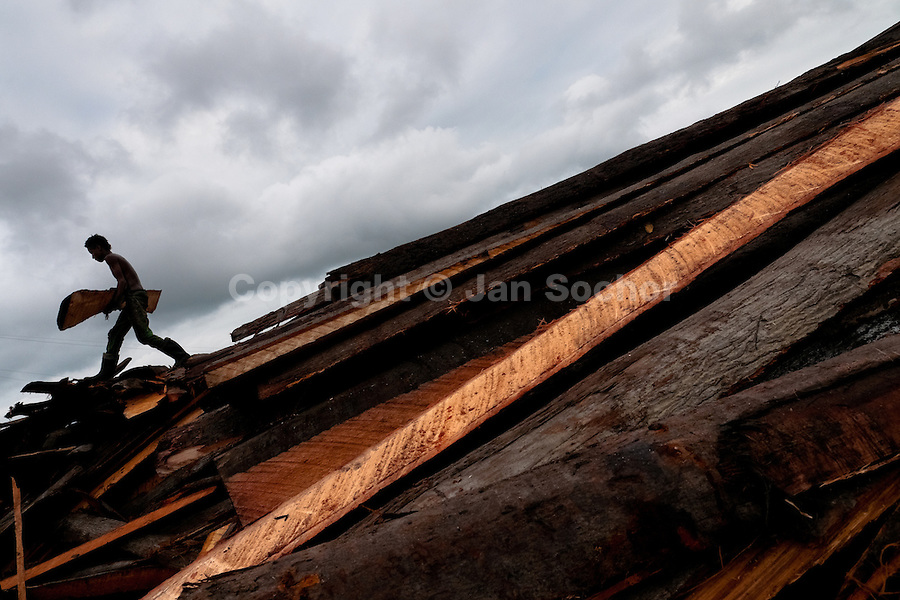 A Colombian worker, carrying a plank, walks on a pile of boards at a sawmill in Tumaco, Colombia, 17 June 2010. Tens of sawmills located on the banks of the Pacific jungle rivers generate almost half of the Colombia's wood production. The wood species processed here (sajo, machare, roble, guabo, cargadero y pacora) are mostly used in the construction industry and the paper production. Although the Pacific lush rainforest in Colombia is one of the most biodiverse area of the world, the region suffers an extensive deforestation due to the uncontrolled logging in the last years.