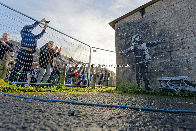 """Pictured: The Banksy graffiti on a garage in Port Talbot, Wales, UK. Thursday 20 December 2018<br /> Re: The artist Banksy has confirmed that a new graffiti piece that has appeared in Port Talbot, south Wales is his.<br /> He announced on Instagram: """"Season's greetings"""" - with a video of the artwork in the Taibach area of Port Talbot.<br /> The image appears on two sides of a garage in a lane near Caradog Street, depicting a child enjoying snow falling - the other side reveals it is a fire emitting ash.<br /> The owner of the garage said he had not slept over fears it might be vandalised."""