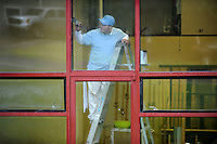 NWA Democrat-Gazette/ANDY SHUPE<br /> Ignacio Arellano of Springdale, a painter with Select Professional Painters in Fayetteville, paints Wednesday, Aug. 19, 2015, around a window at the Nadine Baum Studios in Fayetteville as rain falls outside. More rain is expected this weekend, according to the National Weather Service.