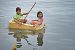 A boy and girl float in the sea in a makeshift boat near Tacloban, a city in the Philippines province of Leyte that was hit hard by Typhoon Haiyan in November 2013. The storm was known locally as Yolanda. The ACT Alliance has been active here and in affected communities throughout the region helping survivors to rebuild their homes and recover their livelihoods.