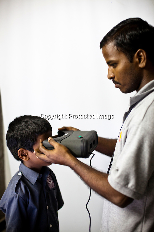 An official assists a young boy to get his iris scanned as part of the enrollment that is on its way in Naagaaram village, outskirts of Hyderabad in Andhra Pradesh, India. India is assigning each one of its 1.2 billion people a unique ID number based on digital finger prints and iris scan. Photograph: Sanjit Das/Panos