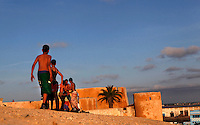 Boys playing on the defensive walls of the Portuguese Fortified city of Mazagan, 16th century, El Jadida, Morocco. El Jadida, previously known as Mazagan (Portuguese: Mazag√£o), was seized in 1502 by the Portuguese, and they controlled this city until 1769. The fortification with its bastions and ramparts is an early example of Renaissance military design. Picture by Manuel Cohen