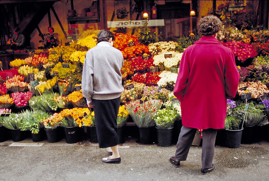 People shopping for flowers displayed at outdoor market, Paris, France. Paris, France.