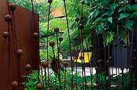 View through rusted steel reed fence towards deck and seating area