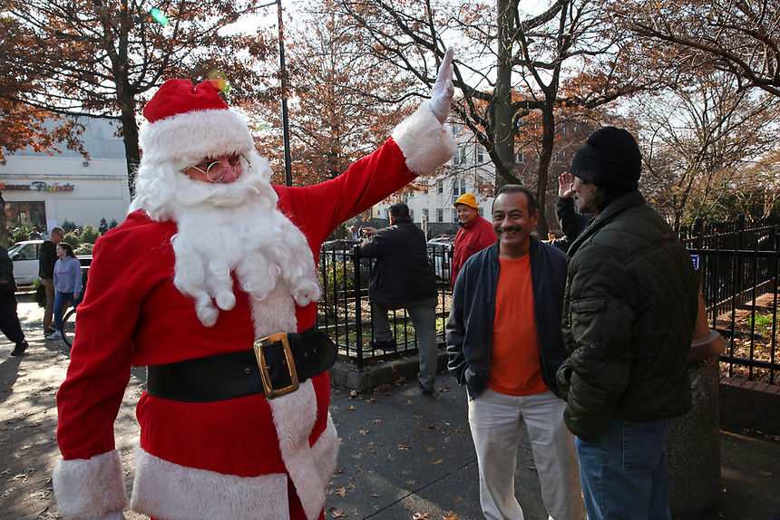 (171203RREI2597) Santa Claus greets the men on the corner on Mt. Pleasant Holiday Festival day.  La Esquina Documentary Project. Latinos have gathered near the 7 - 11 at the corner of Mt. Pleasant St. and Kenyon St. NW. for more than 40 years. Washington DC. Dec. 2 ,2017 . ©  Rick Reinhard  2017     email   rick@rickreinhard.com