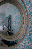 A bedroom decorated in shades blue with patterned wallpaper and a double bed with a upholstered headboard seen reflected in a circular mirror on the wall.