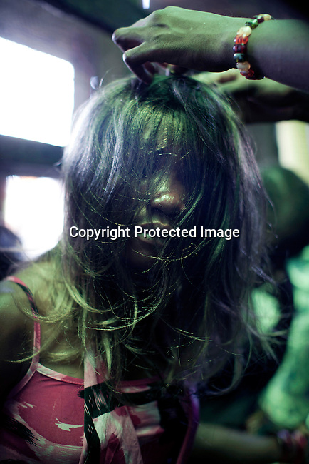 KINSHASA,DRC - OCTOBER30: Esther Yandakwa, a 13-year old homeless child has her hair done in the central market of Kinshasa, DRC. She has lived on the streets since she was 6-7 years old and is dependent on prostitution to survive. She is walking the streets of Kinshasa to look for customers. She uses drugs and lives with a group of other homeless people in central Kinshasa. Thousands of children live on the streets of Kinshasa. Esther has been in and out orphanages or but she is only happy living in the mean streets of Kinshasa. (Photo by: Per-Anders Pettersson)
