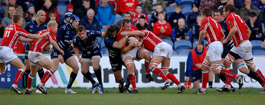 Photo: Richard Lane..Sale Sharks v Llanelli Scarlets. EDF Energy Anglo Welsh Cup. 02/12/2006. .Scarlets' Nathan Thomas is tackled by Sale's Sebastien Chabal.
