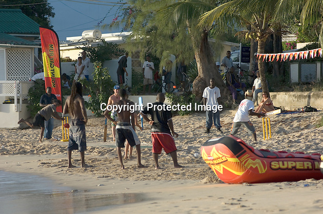 The batsman is about to strike the ball out to sea during an evening cricket match on Mullins Beach.