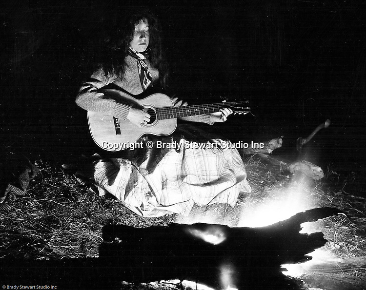 North East PA: Margaret Gray in front of a campfire playing her guitar.  Brady Stewart loved to experiment with cameras and film and the campfire scenes were unique.  He determined the right amount of flash powder along with exposure to capture Clark, the fire and his surroundings.
