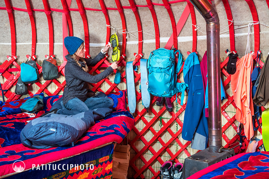 A woman inside a yurt while on a ski touring trip in Kyrgyzstan