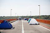 Kroatische Sicherheitskräfte haben die Brücke mit einem Bagger und einigen Einsatzwagen blockiert. Da die Flüchtlinge nicht nach Serbien zurückkehren wollen, harren sie bei 37 Grad in der Mittagssonne aus und bauen sich sogar Zelte.