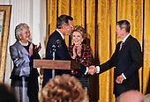 United States President George H.W. Bush shakes hands with former U.S. President Ronald Reagan as he officiates at the presentation of the official portraits of President Reagan and first lady Nancy Reagan  in the East Room of the White House in Washington, D.C. on November 15, 1989.  From left to right: Barbara Bush, President Bush, Nancy Reagan, former President Reagan.<br /> Credit: Ron Sachs / CNP