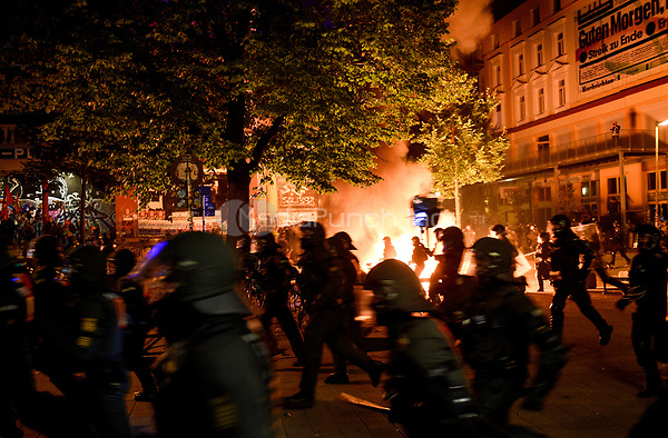 Police in riot gear run past a fire during demonstrations against the G20 summit in Hamburg, Germany, 6 July 2017. The heads of the governments of the G20 group of countries are meeting in Hamburg on the 7-8 July 2017. Photo: Axel Heimken/dpa /MediaPunch ***FOR USA ONLY***