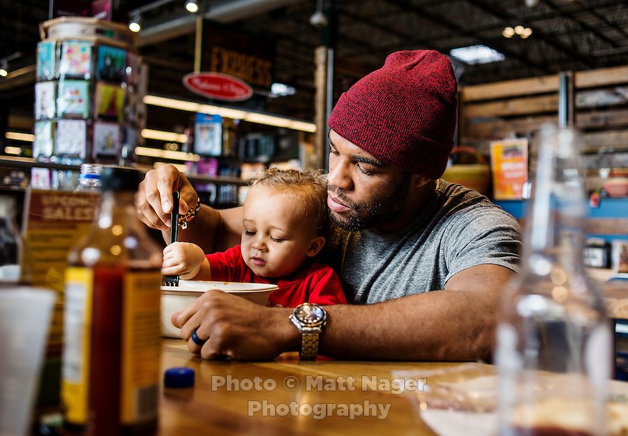 Olympic Gold champion wrestler Jordan Burroughs (cq) with his son Beacon Burroughs (cq, age 19 months) eating lunch at Whole Foods in Lincoln, Nebraska, Friday, February 12, 2015. Burroughs is training for the upcoming 2016 olympic games in Rio de Janeiro, Brazil where he hopes to win another gold medal. <br /> <br /> Photo by Matt Nager