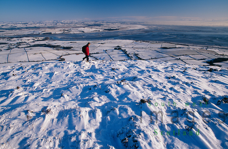 Winter hill walking in snow Scotland walker on Knockendock on way up Criffel looking down on Nith Estuary, Solway Firth and across Dumfriesshire to Moffat Hills