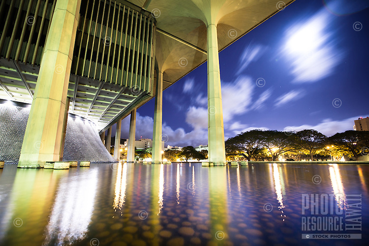 A full moon and streaking clouds light up the sky behind O'ahu's State Capitol building.
