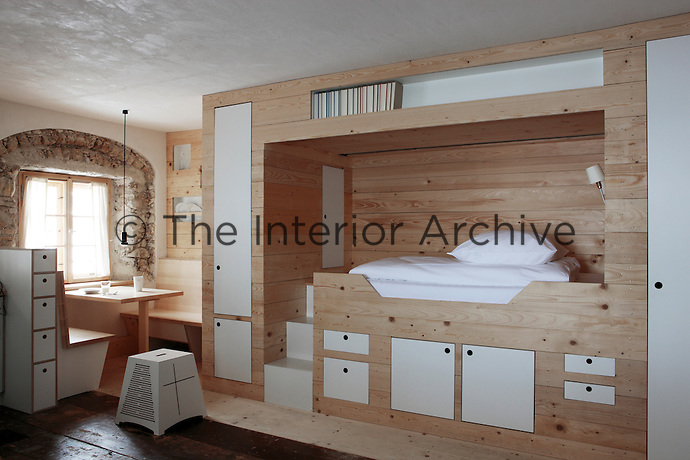 In this cosy bedroom there are integrated steps to the box bed and a table and bench have been built underneath the window