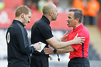 Rotherham United manager Paul Warne (C)  protests to referee Keith Stroud (R) about an alleged handball committed before the goal scored by Kyle Naughton of Swansea City during the Sky Bet Championship match between Swansea City and Rotherham United at the Liberty Stadium, Swansea, Wales, UK. Friday 19 April 2019