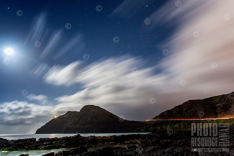 The full moon lights up tidal pools, the open ocean, Makapu'u Point and the Ko'olau mountains under a starry night sky streaked with clouds, seen from Makapu'u Beach, Waimanalo, O'ahu.