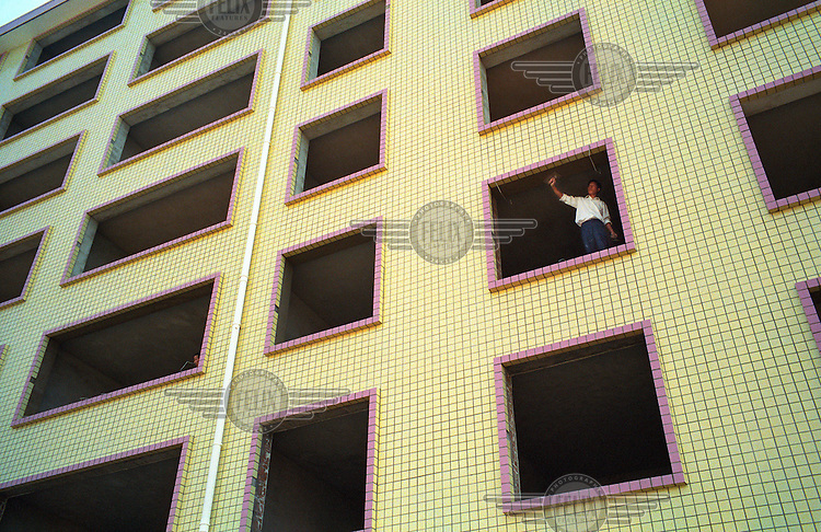 A man looks from the window of an unfinished housing complex in Guanzhou.