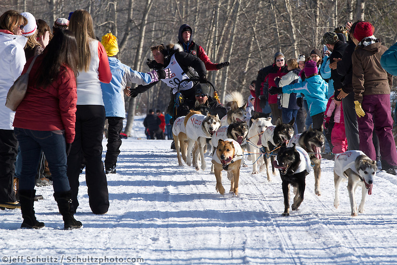 Cindy Abbott and team run past spectators on the bike/ski trail during the Anchorage ceremonial start during the 2013 Iditarod race.    Photo by Britt Coon/IditarodPhotos.com
