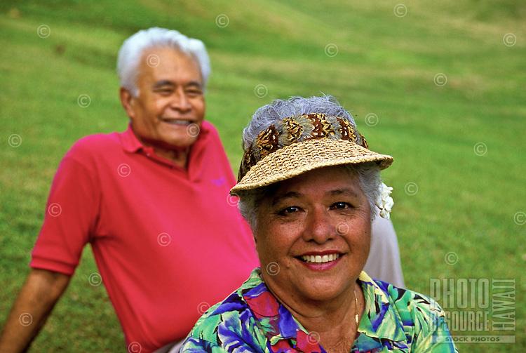 Smiling senior Hawaiian man and part-Hawaiian woman wearing visor with feathered hatband