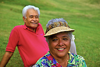 Smiling senior Hawaiian man and part-Hawaiian woman wearing visor with feathered hatband