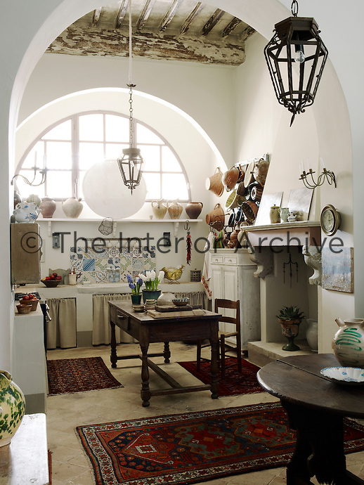 Antique pottery bowls are displayed on a rack on one side of a stone sink in the kitchen