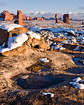 Melted snow in a shallow pothole reflects the Navajo sandstone rock, with Balanced Rock in Arches National Park in the background with the La Sal Mountains, near Moab, Utah, USA.