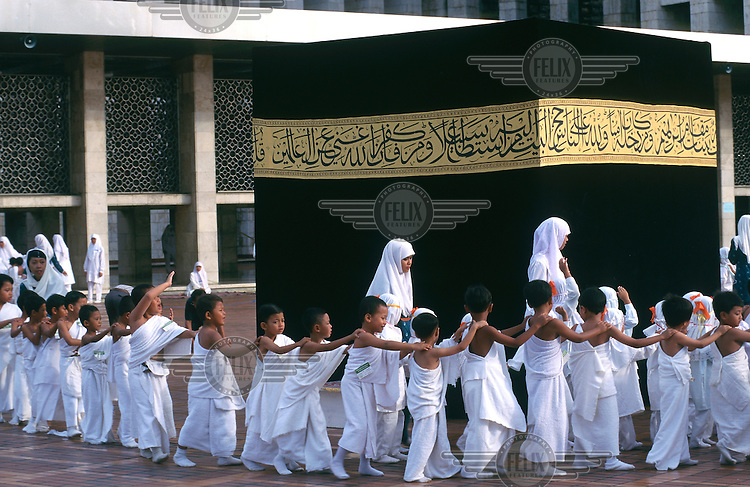 Indonesia, Java, Jakarta..Religion. Islam. Education. Muslim chidren taking part in a mock Haj circling a copy of the Kaabah in the courtyard of the Istiqlal mosque..©Mark Henley