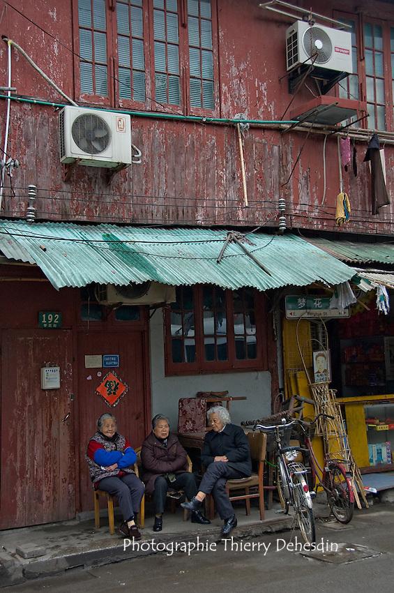 De vieilles copines qui papotent dans la rue devant leur maison..Shanghai, février 2006.