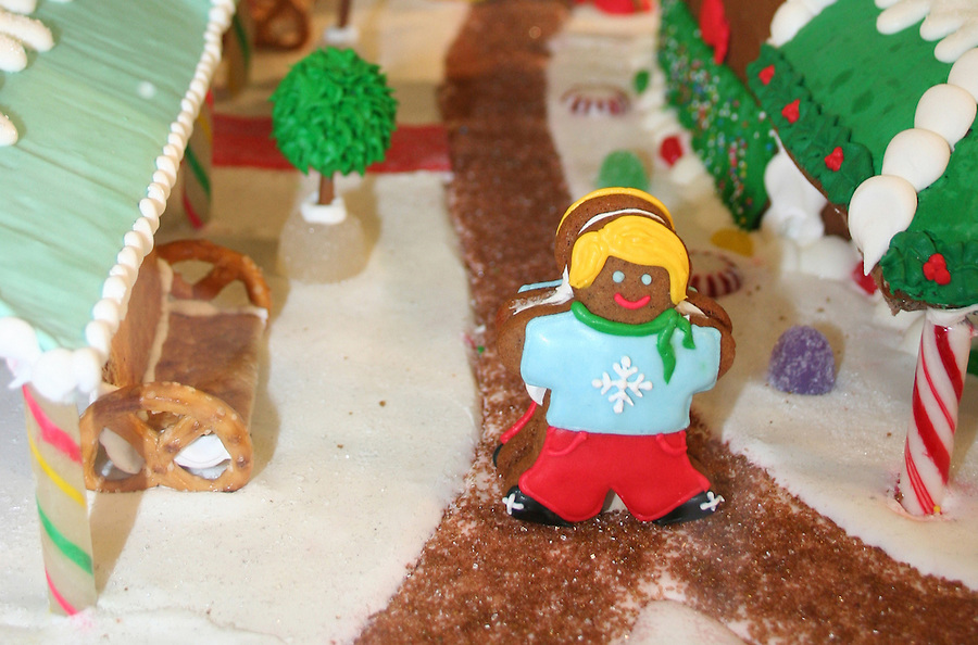 Gingerbread cookie girl set in village made of candy and cookies