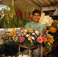 Flower vendor in Mexico City, Mexico--series - young man with flower arrangement and cut flowers in background, flower market. Mexico City Distrito Federal, Mexico.