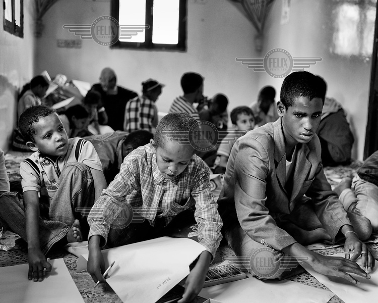 Children writing on sheets of paper at a school catering for migrants, most of whom are from Somalia. The United Nations Refugee Agency (UNHCR) has raised concerns over the record numbers of Ethiopians and Somalis flocking to Yemen, despite the deteriorating security situation there. In 2011 103,000 migrants crossed the Gulf of Aden and Red Sea. Most arrive dehydrated and malnourished and face physical and sexual attacks. They are regularly robbed and attacked by smugglers and traffickers.