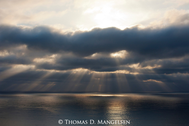 Rays of light shine through the clouds over the Pacific Ocean at sunset in La Jolla, California.