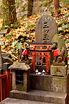Private worship shrine altar, Tsuka, with Kitsune, messenger foxes. One of the thousands little Shinto shrines at Fushimi Inari Taisha head shrine in Fushimi Ward, Kyoto, Japan