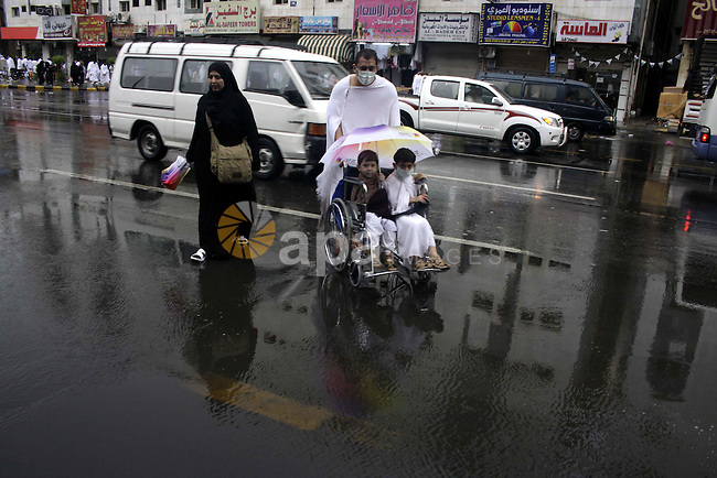 Muslim pilgrims walk in the streets during heavy rains that disrupted the annual Hajj pilgrimage and cut electricity and flooded low areas in the holy city of Mecca on November 25, 2009. Some 2.5 million Muslims from more than 160 countries converge annually on the Islamic holy cities of Mecca and Medina in western Saudi Arabia. Photo by Ashraf Amra