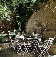 A simple garden table and white chairs has been set in the shade on a small terrace