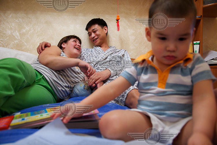 SHI Xiaojun (center), a Chinese acupunturist, is at home with his wife Natalia and their son Mark in the city of Blagoveshchensk on the border with China.