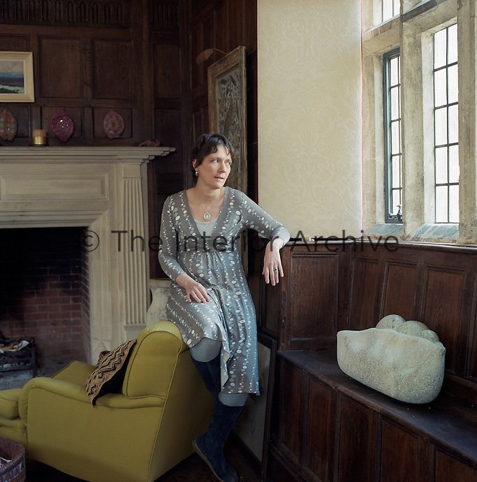 "Rosie Pearson pictured in the window seat of the wood-panelled dining room which displays a carving in Connemara marble by sculptor Anthony Turner entitled ""Thee Peas in a Pod"""