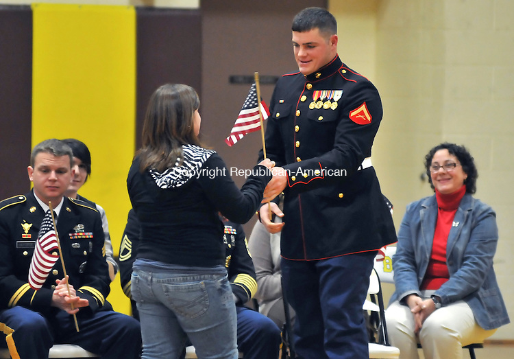 THOMASTON, CT-10 NOVEMBER 2009-111009JS16-Lance Cpl. Jon Conlon receives an American flag from his sister Olivia during a ceremony Tuesday at Thomaston High School. 20 Thomaston High School graduates and residents who have, or are, serving in the military, were honored during the ceremony.<br /> Jim Shannon Republican-American