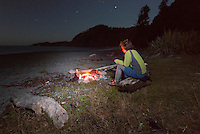 Female tramper enjoing fire while camping on beach at Smoothwater Bay near Jackson Bay after sunset, South Westland, West Coast, World Heritage Area, South Island, New Zealand