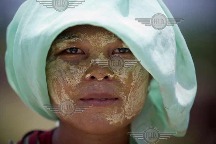 Melda, a labourer in a palm oil plantation, wears a traditional sandal wood paste on her face to protect her skin from the harsh sun as she clears debris from the fields.