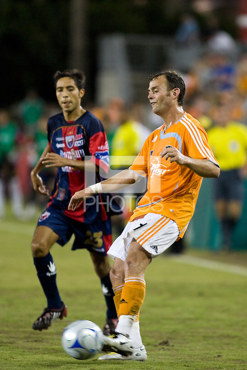 Houston Dynamo  midfielder Brad Davis (11) crosses the ball as Atlante FC defender Gerardo Castillo (23) attempts to cut off the angle. Houston Dynamo defeated Atlante FC 4-0 during the group stage of the Superliga 2008 tournament at Robertson Stadium in Houston, TX on July 12, 2008.