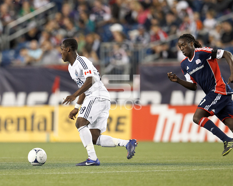 Vancouver Whitecaps FC midfielder Gershon Koffie (28) dribbles as New England Revolution midfielder Shalrie Joseph (21) closes. In a Major League Soccer (MLS) match, the New England Revolution defeated Vancouver Whitecaps FC, 4-1, at Gillette Stadium on May 12, 2012.