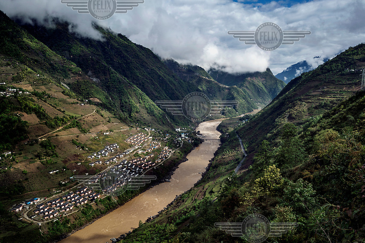 Mian Gu village, a government housing project to encourage people living in the mountains to live near the riverside and prevent deforestation, on the west bank of the Nujiang River.