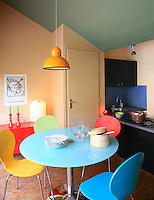 The kitchen-diner is a riot of colour with each chair painted a different hue