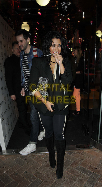 Vanessa White of The Saturdays .attended the Monki store launch party, Monki, Carnaby Street, London, England, UK, 8th March 2012..full length black  knee high boots leggings jacket blazer  cross necklace  clutch bag sheer bra yellow .CAP/CAN.©Can Nguyen/Capital Pictures.